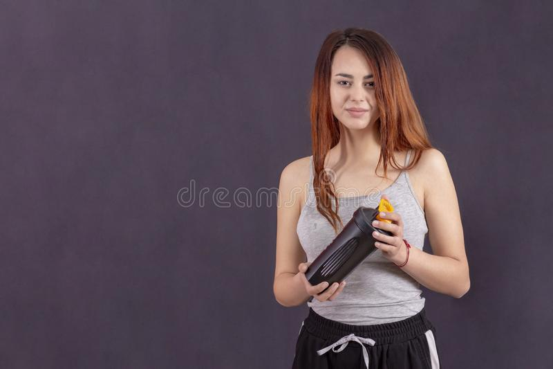 Active girl after jogging drinks. sweat on his forehead. Mike in sweat is wet. smiling satisfied with playing sports royalty free stock photos