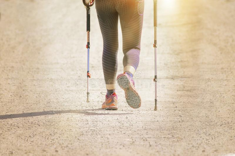 Active girl practicing nordic walking with sticks outdoors against a sun flare. Empty copy space. For Editor`s content royalty free stock photography