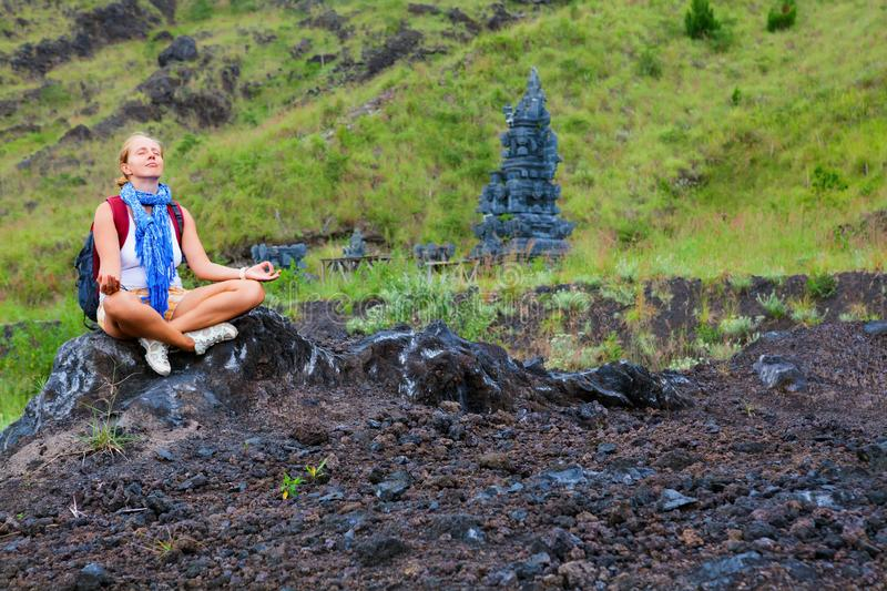 Active girl relaxing in yoga meditating pose during volcano hiking stock photo