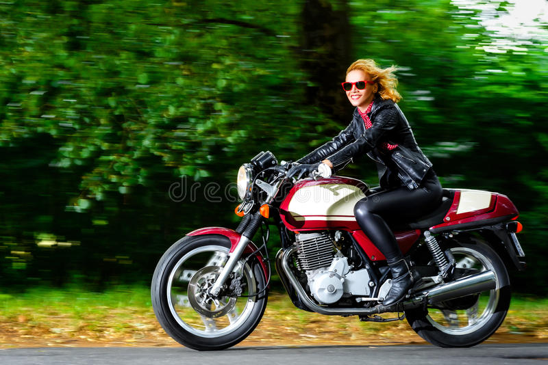Active girl riding on the motorbike, slow motion stock photography