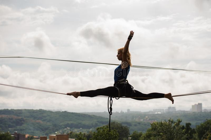 Active girl sitting on twine on the slackline rope stock images