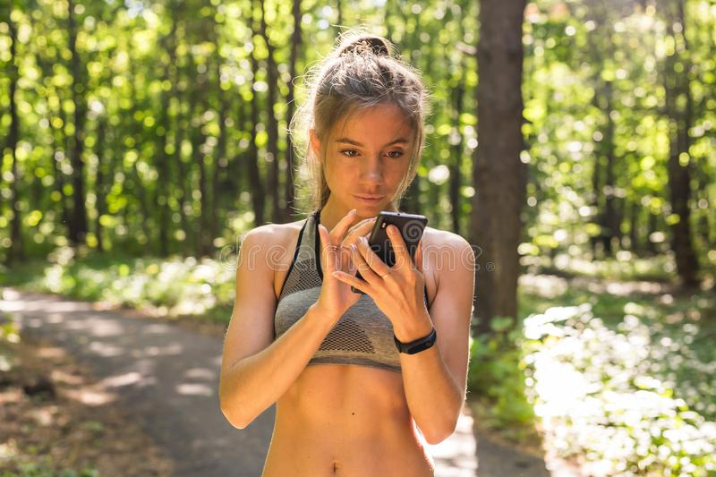 Active girl using fitness tracker smart watch jogging on summer nature outdoors looking at health data during sports. Activity royalty free stock photo