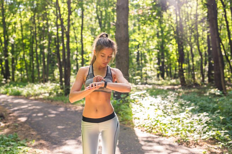 Active girl using fitness tracker smart watch jogging on summer nature outdoors looking at health data during sports. Activity royalty free stock photography