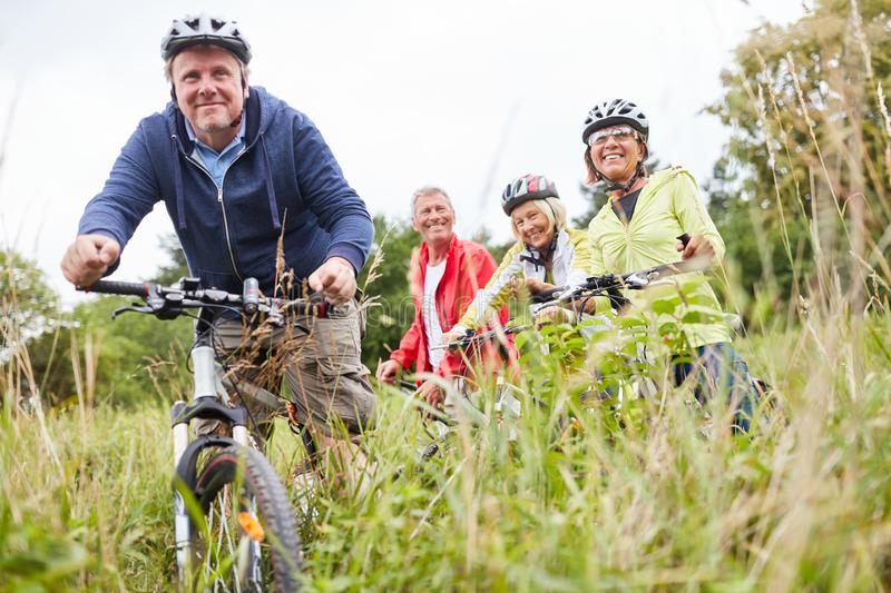 Group of seniors riding bikes together. Active group of seniors together while cycling in nature stock photography
