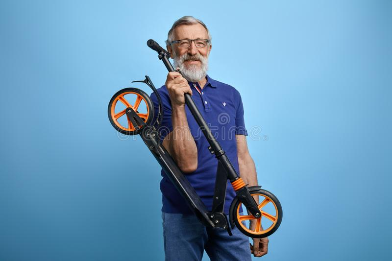 Active handsome old man in stylish casual clothes is going to ride scooter. stock photos