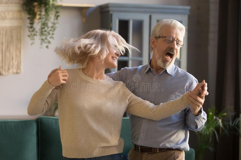 Active happy mature couple have fun dancing at home stock photography