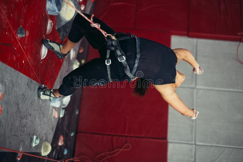 Active happy woman overhanging on tightrope in the training climbing center stock photo