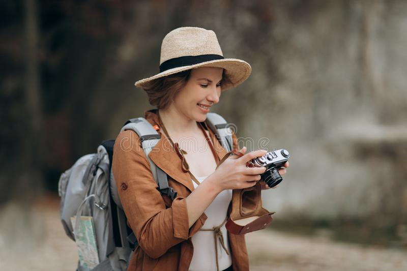 Active healthy Caucasian woman taking pictures with an vintage film camera on a forest rocks stock photos