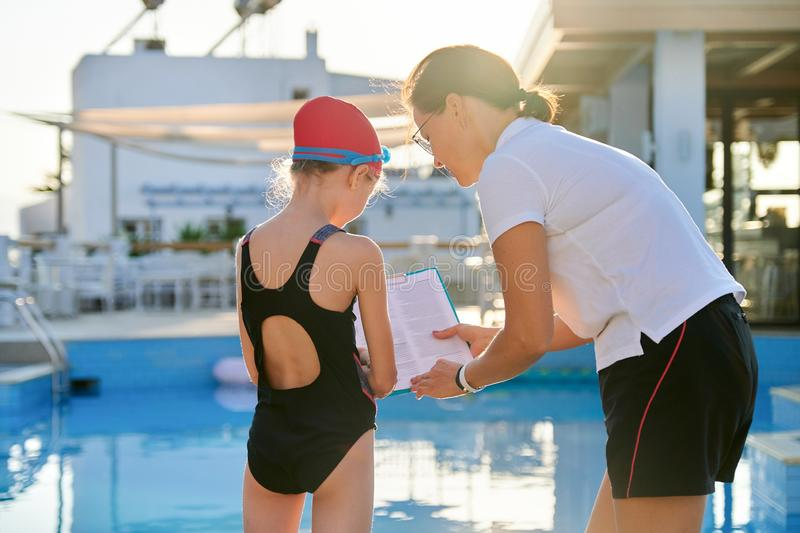 Woman trainer talking to girl child near outdoor pool stock photo