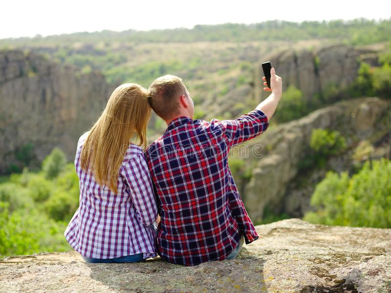 Cute romantic couple taking a selfie. Tourists taking photographs on a natural background. Youth and technology concept. stock image