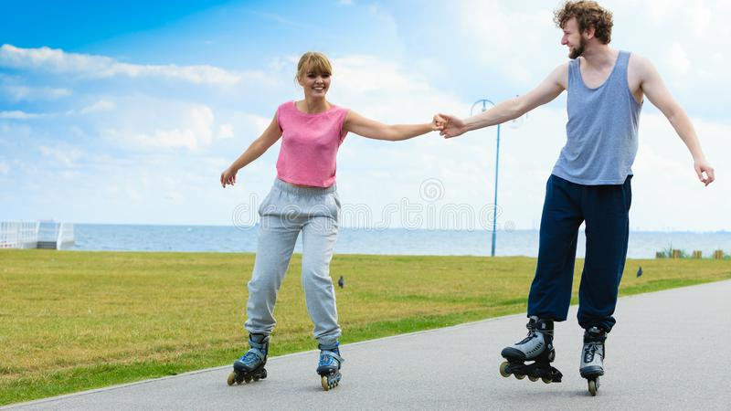 Young couple holding hands while rollerblading royalty free stock photos