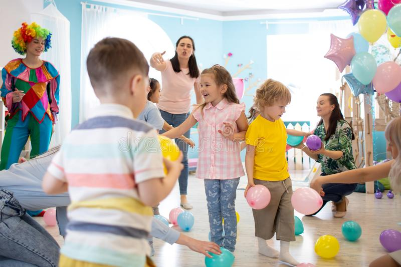 Active kids having fun and playing with multicolored balloons in daycare royalty free stock photo
