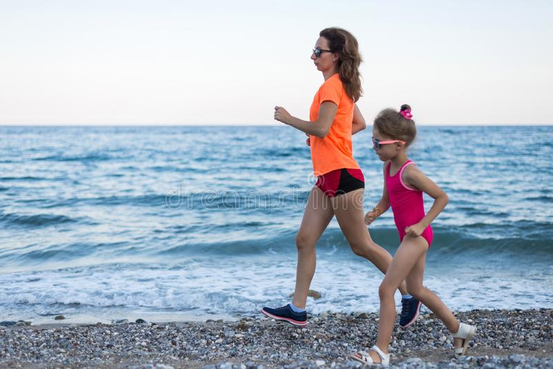 Active lifestyle: morning jogging along the beach. Mom and daughter run along the beach stock image