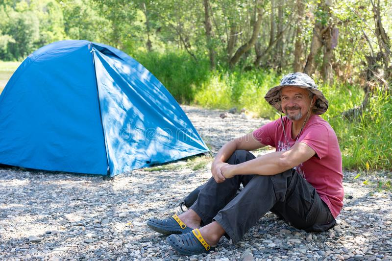 Active lifestyle in old age concept. camping, tourism in the elderly grow. an old man in a hat smiles and sits near the tent stock image