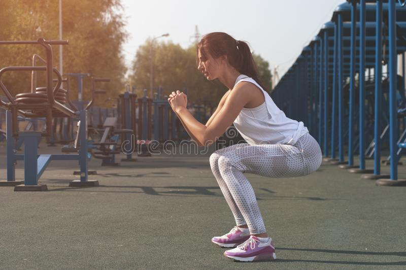 Slim brunette woman exercising in outdoor gym stock photo