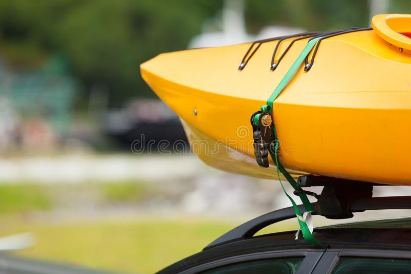 Car with canoes on top. Active lifestyle sport concept. Car with kayak yellow canoe on top roof ready to transportation stock photos