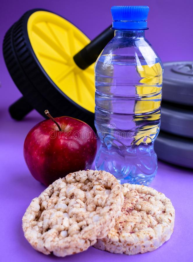 Active lifestyle sport water apple oatmeal loaves gymnastic wheel. Healthy diet food apple oatmeal loaves slim isolated yellow slenderness red water active royalty free stock photo
