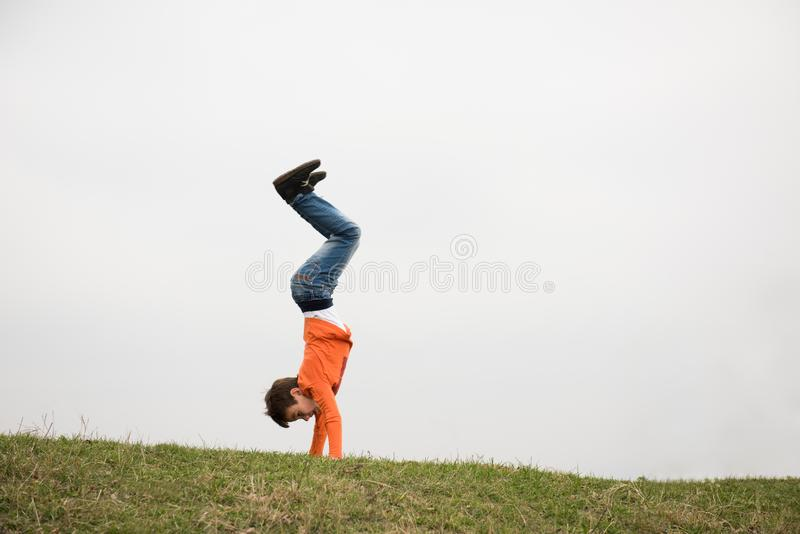 Active little caucasian boy in jeans standing on hands upside down on green grass outdoors with copy space royalty free stock photography