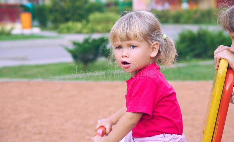 Active little Caucasian girl in a red t-shirt and with tails on playground - closeup shot royalty free stock image