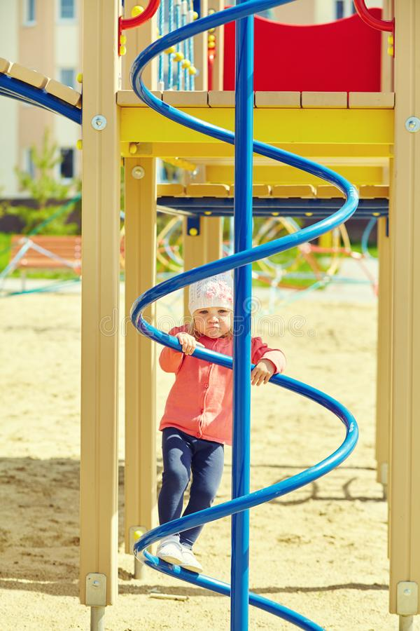 Active little girl on playground. child playing outdoors in the summer stock photo