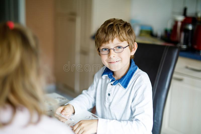 Active little school kid boy with glasses playing card game with his girl friend at home. Creative and funny leisure for royalty free stock images