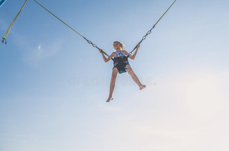 Child jumping high  in the jumping attraction. Active little young teen girl jumping in trampoline high into the blue sky safed with  elastic safety belt royalty free stock photo