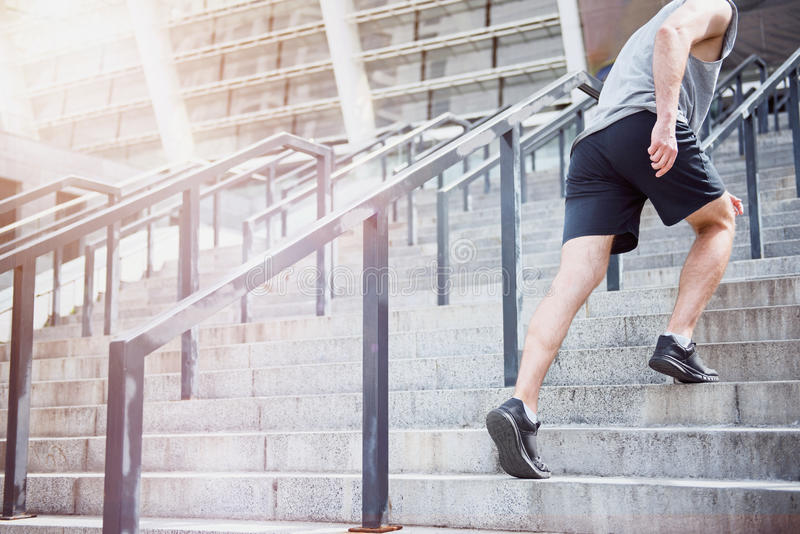 Active man climbing up the stairs in a sportswear stock image