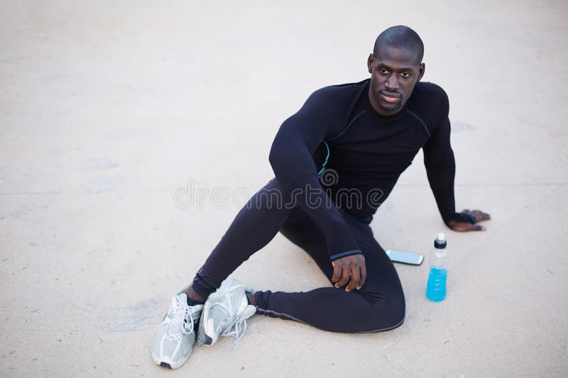 Active man having break after fitness training. Smiling dark skinned runner resting after workout outdoors,male runner in active clothes taking break after run royalty free stock photos