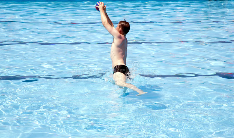Active man playing ball in big outdoor swimming pool royalty free stock photo