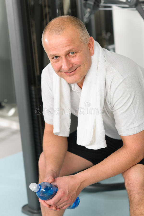 Active man relax sitting by fitness machine. Active man relax at gym sitting by fitness machine royalty free stock images