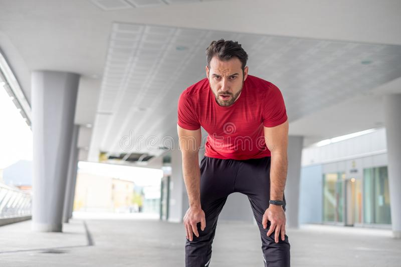 Active man resting during urban running training stock photography