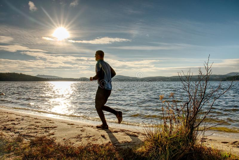 Active Man running at lake. Travel adventure healthy lifestyle concept vacations, athletic person stock images