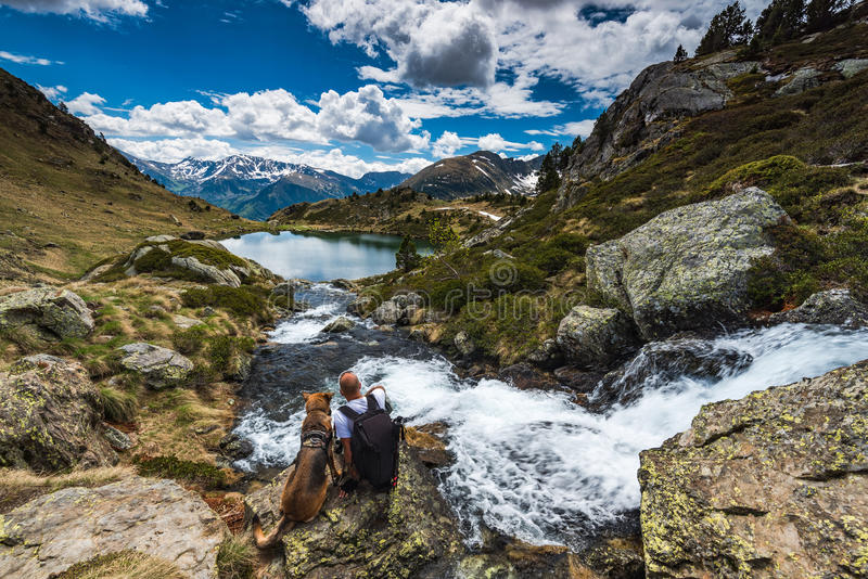 Active man sit on rock with dog while trekking. In Pyrenees royalty free stock photo