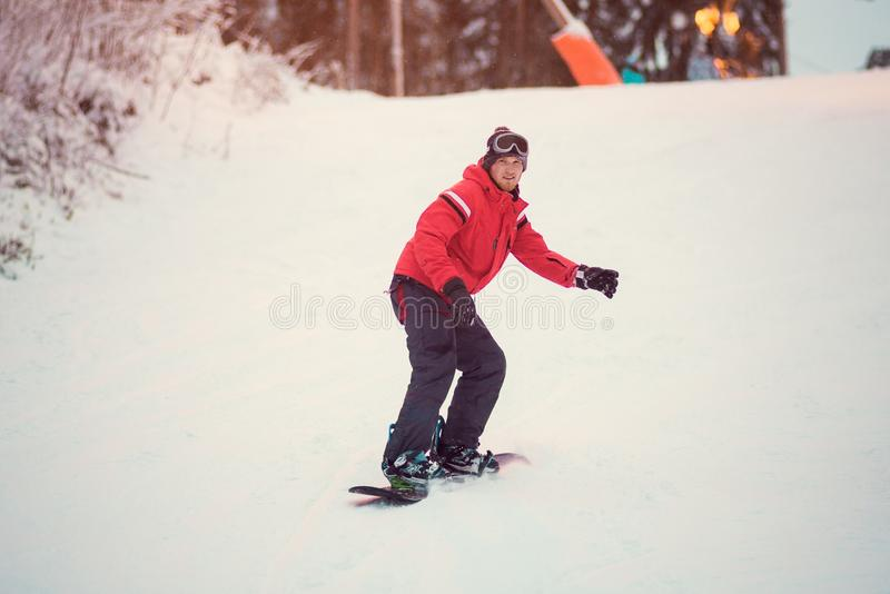 Active man snowboarder in red jacket riding on slope, snowboarding royalty free stock photo