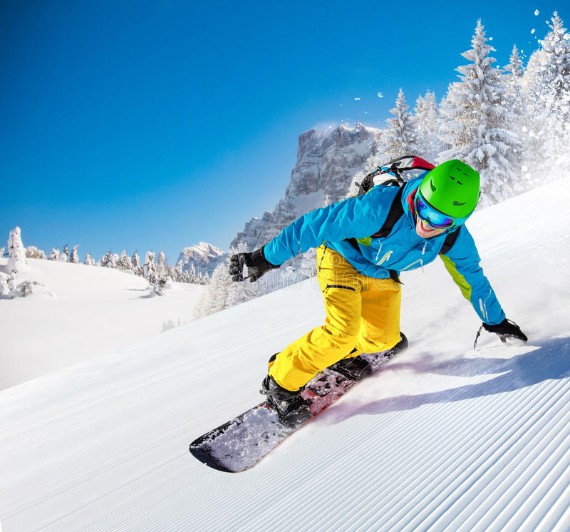 Man snowboarder riding on slope. royalty free stock photos
