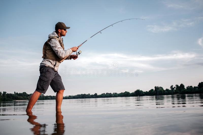 Active man is standing in shallow and fishing. He holds fly rod in hands. Man is twisting around reel to make spoon stock photos