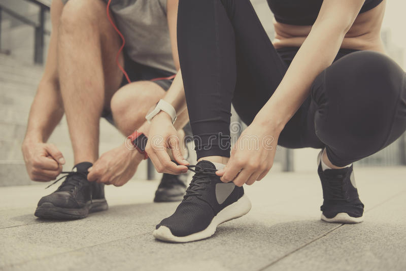 Active man and woman tying their shoelaces royalty free stock image