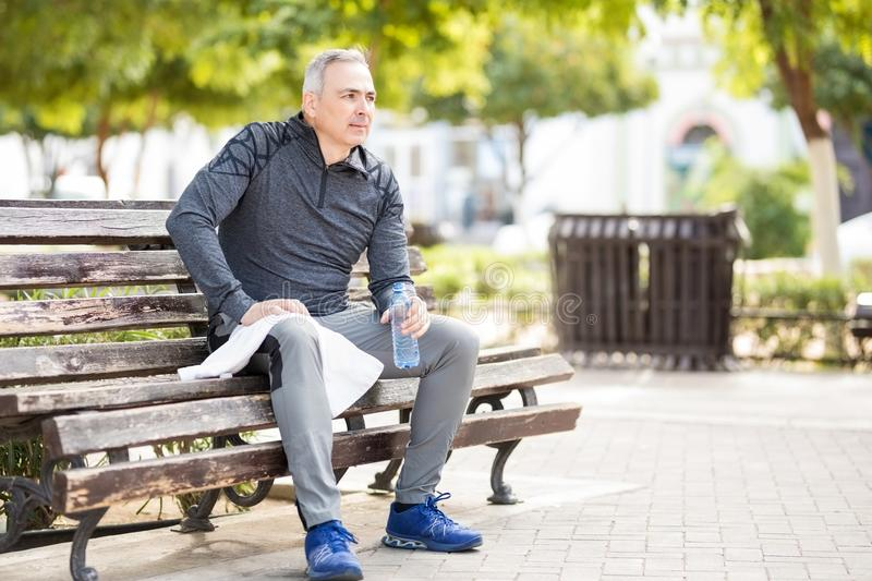 Healthy middle aged man resting after jogging in the park stock photos