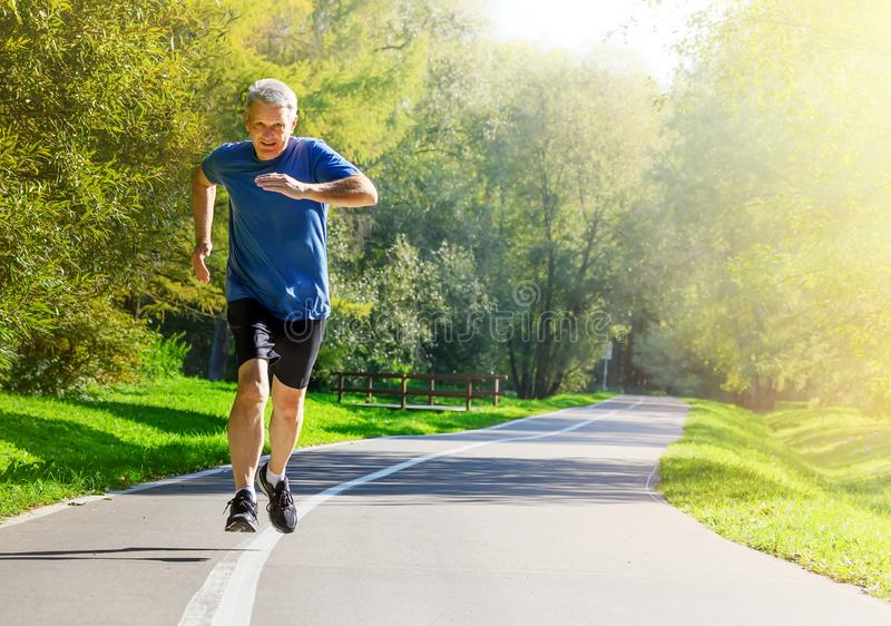 Active middle aged man running in public park stock photography