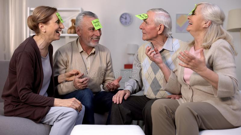 Active old people playing who am i game sitting in cozy living room, leisure. Stock photo stock photo