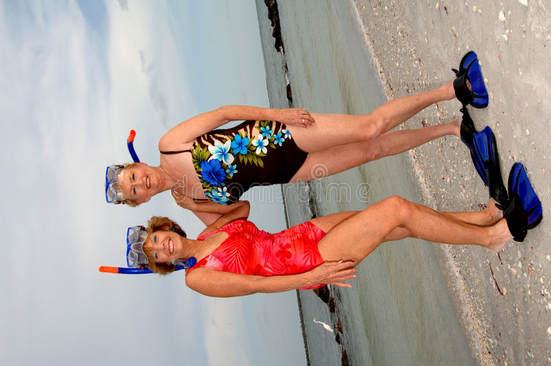 Active older women snorkel. Two senior women in swim suits and snorkel gear on the beach stock photography