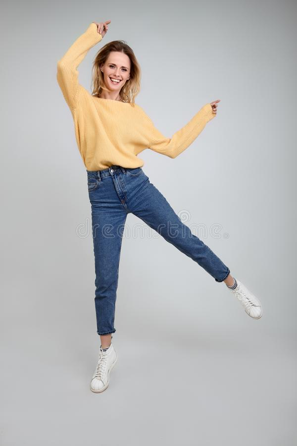 Active optimistic girl photographed at studio, jumps in air over white background, has broad smile, dressed in fashionable clothes stock photos