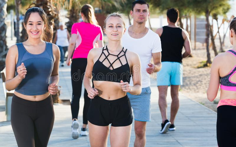Active people during running training. Active smiling people during running training in daytime royalty free stock image