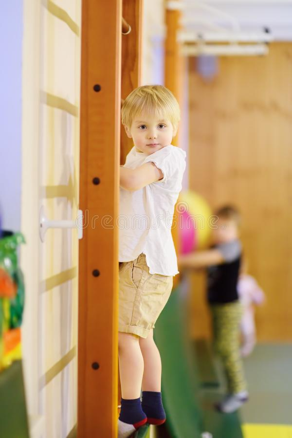 Active preschool boy during lesson in indoor sports hall/gym class stock image