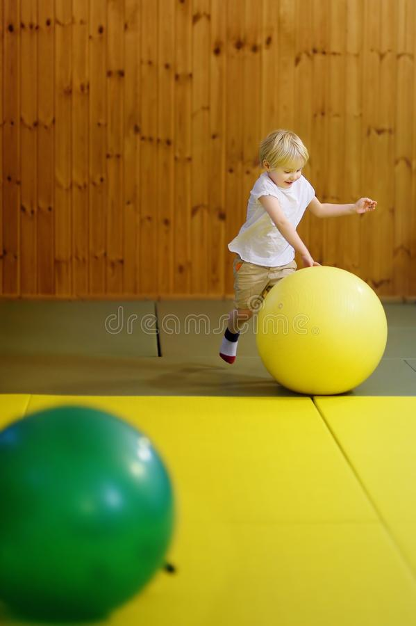Active preschool boy playing with big ball in indoor sports hall/gym class. Active preschool boy playing with big ball in indoor sports hall. Kids active game royalty free stock photos