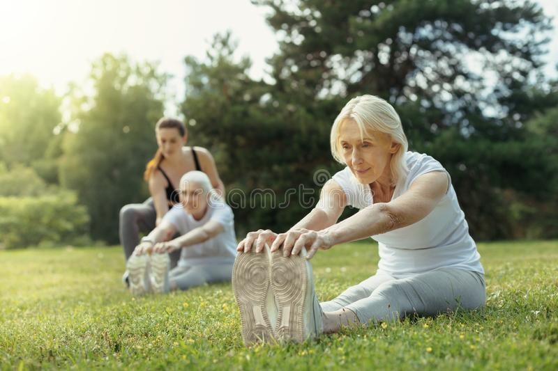 Active retired lady stretching her back while training stock photography