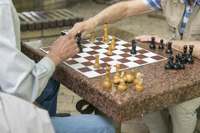 Active retired people, old friends and free time, seniors having fun and playing chess game at park. Waist up. Old men playing. Chess in the park royalty free stock photos