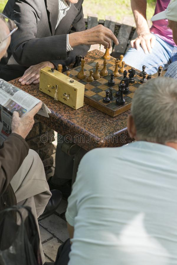 Active retired people, old friends and free time, seniors having fun and playing chess game at park. Waist up. Old men playing. Chess in the park. vertical royalty free stock image