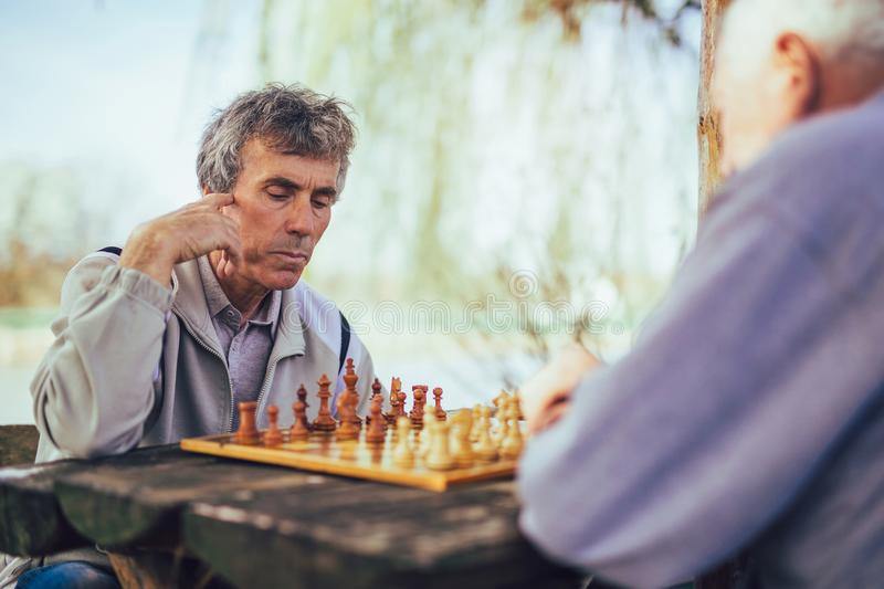 Senior men having fun and playing chess at park. Active retired people, old friends and free time, two senior men having fun and playing chess at park royalty free stock images