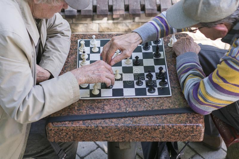 Active retired people, old friends and free time, two seniors having fun and playing chess game at park. Old men are playing chess stock photo